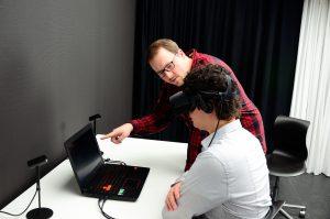 Auf dem Bild sieht man Dennis mit einer Virtual Reality Brille auf dem Kopf. Thorsten zeigt ihm etwas auf dem Laptop obwohl Dennis nichts sehen kann.
