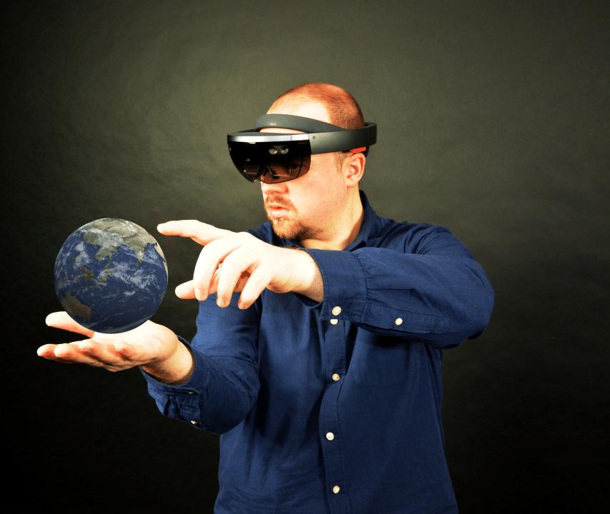 Bild eines Menschen, der eine Microsoft HoloLens trägt und ein 3D Modell der Erde auf seiner Hand bearbeitet.