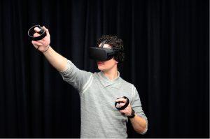 Mensch mit Virtual Reality Brille, der gerade eine Virtual Reality Applikation genießt.